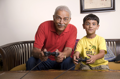 grandfather playing video game with child